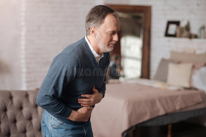 老人以强的胃疼痛 库存图片
