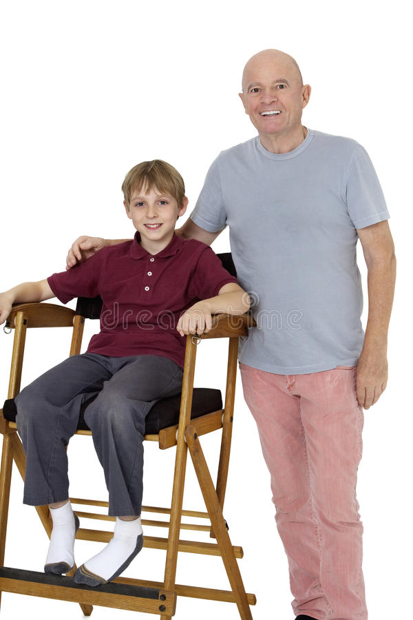 老人画象有青春期前的男孩的坐在白色背景的主任的椅子 免版税库存照片
