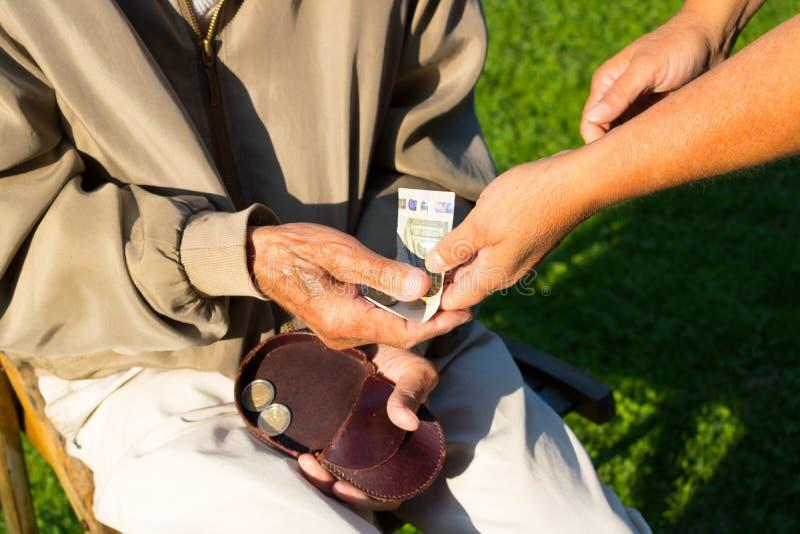 老人` s递拿着欧洲钞票 奋斗的领抚恤金者 库存照片