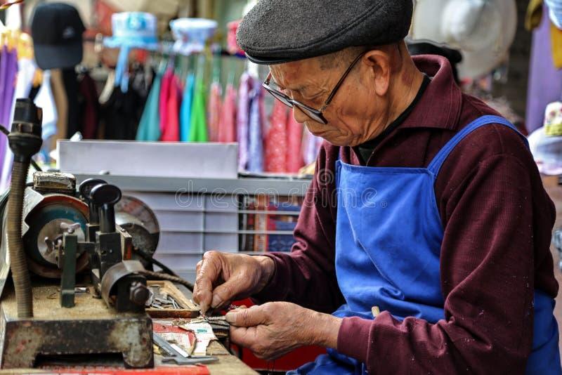 老人granding的钥匙在yuantong镇在四川,瓷 免版税库存图片