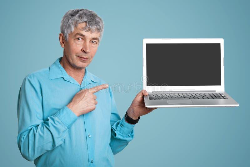 老人wrinked在正式衬衣举行现代便携式的便携式计算机的英俊的男性有您的文本或广告的空白的拷贝屏幕的 库存照片
