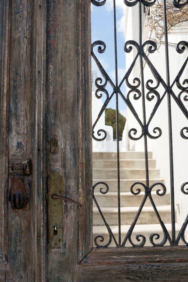 老以手的形式铁生锈的门把手 一个房子的布朗木门在Tira希腊,在海岛上  免版税库存图片
