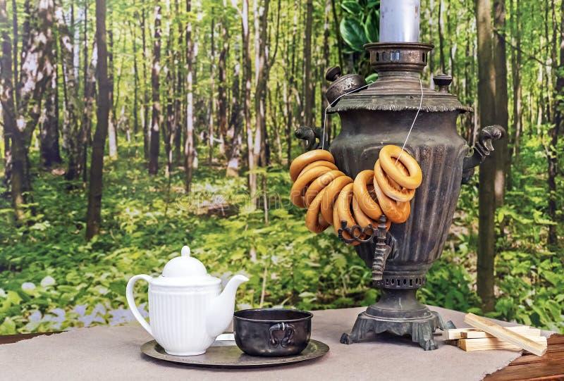 老俄国俄国式茶炊用在一张木桌上的百吉卷 库存图片