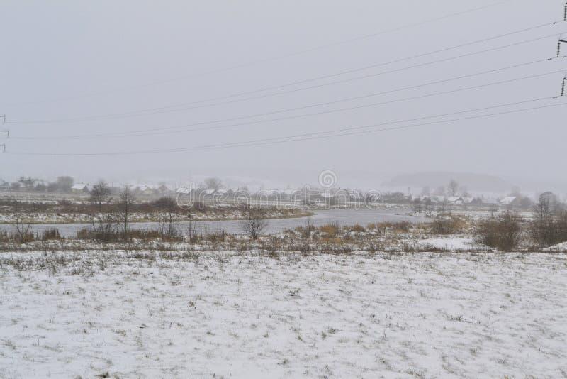 老俄国村庄风景,与河的农村冬天场面和木传统房子 免版税库存照片