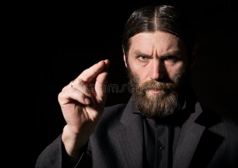 老信徒资深祷告,祈祷在黑暗的背景的有胡子的老人 免版税图库摄影