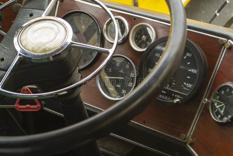 老公共汽车的客舱 葡萄酒仪表板 皮革方向盘 免版税库存图片
