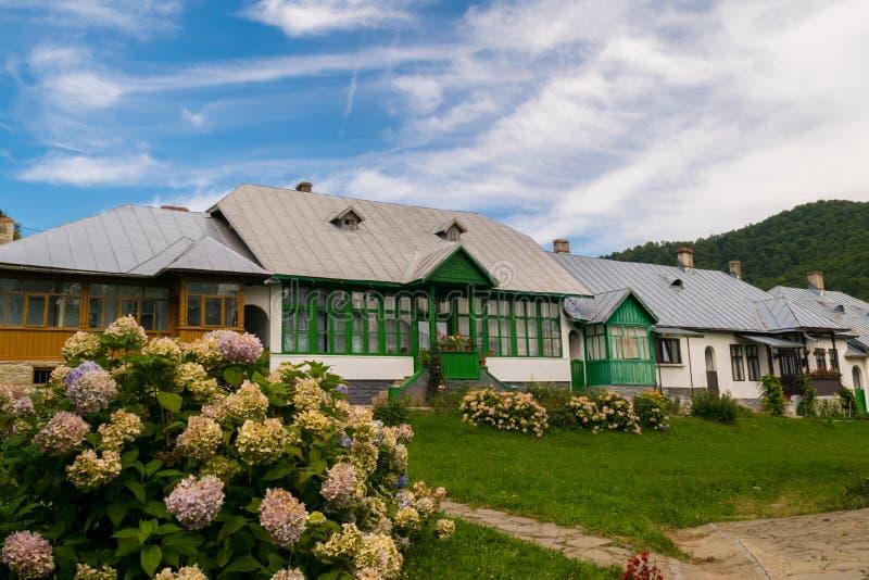老典型的罗马尼亚语安置与被绘的木门的门面和窗口、绿草和花 库存照片