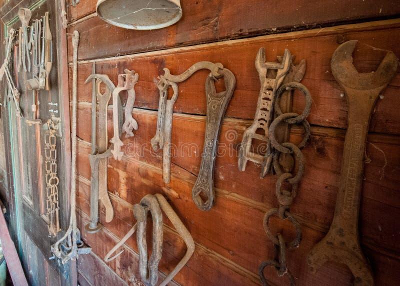 老农厂工具在墙壁上垂悬了 库存照片