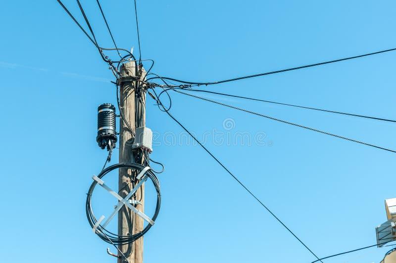 老减速火箭的与许多电供应导线或缆绳的样式木杆与蓝天背景的电话通信的 免版税图库摄影