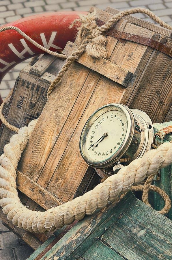 老减速火箭的对象仿古质地背景木板箱、计时表和绳索 图库摄影
