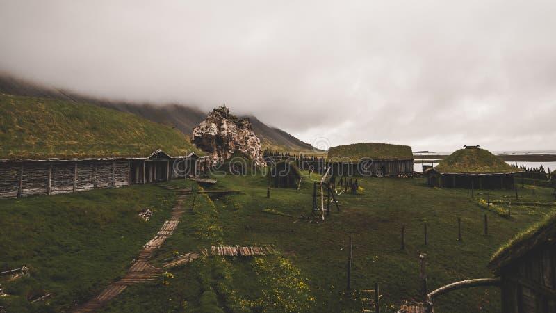 老北欧海盗村庄在有有雾的小山的冰岛 在草盖的老木大厦 免版税库存图片