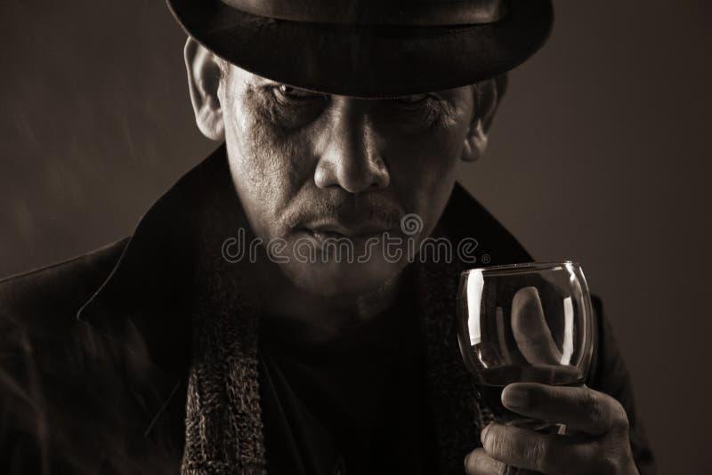 老匪徒和一杯酒 库存图片