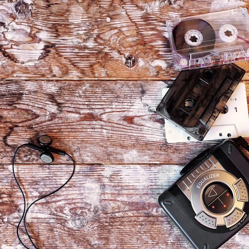 老卡式磁带播放机和录音磁带在木背景 免版税库存图片