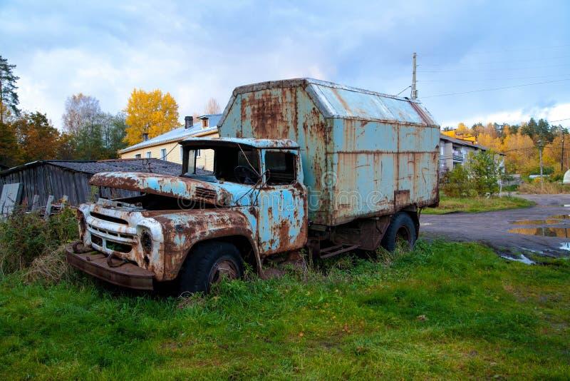 老卡车在房子附近居住它的在草坪的天 免版税库存图片