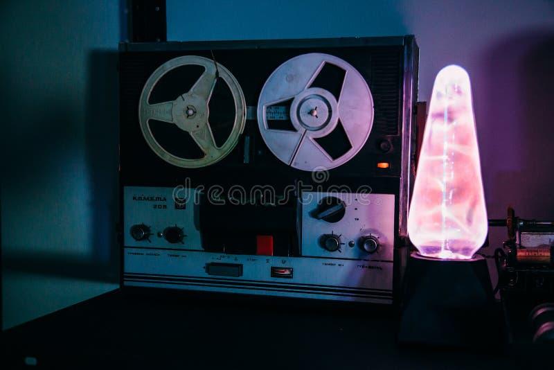 老卷轴减速火箭的录音机和静电等离子特斯拉灯在暗室 库存照片