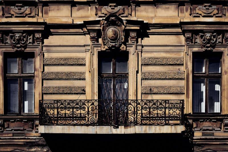 老历史的房子修造的门面有经典古色古香的曲拱窗口和舒适阳台的 免版税库存照片