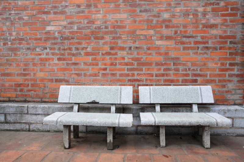 老双胞胎椅子临近脏的红砖墙壁 库存图片
