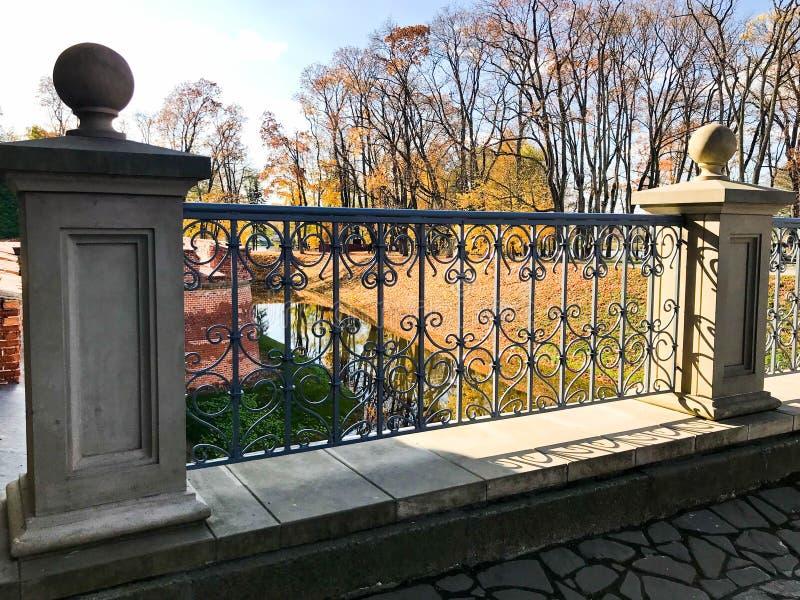 老古老一座桥梁的葡萄酒美丽的石锻铁栏杆有样式的在河和树的背景 免版税库存照片
