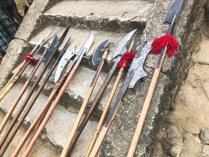老古老中世纪冷的武器,轴,戟,刀子,有木把柄的剑在城堡的石步舔 免版税库存照片