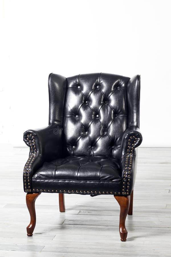 老古色古香的黑皮革翼胳膊椅子 免版税库存图片