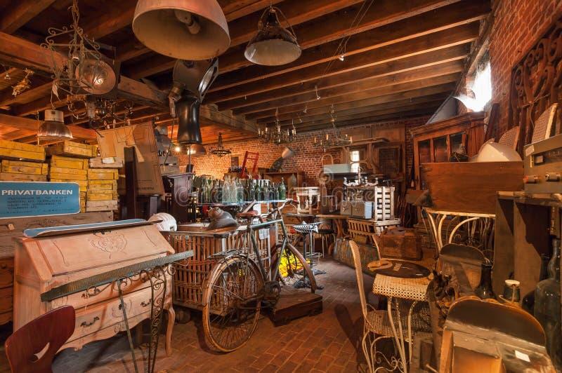 老古董店顶楼与许多的葡萄酒器物、装饰、木家具、减速火箭的自行车和许多细节 免版税库存照片