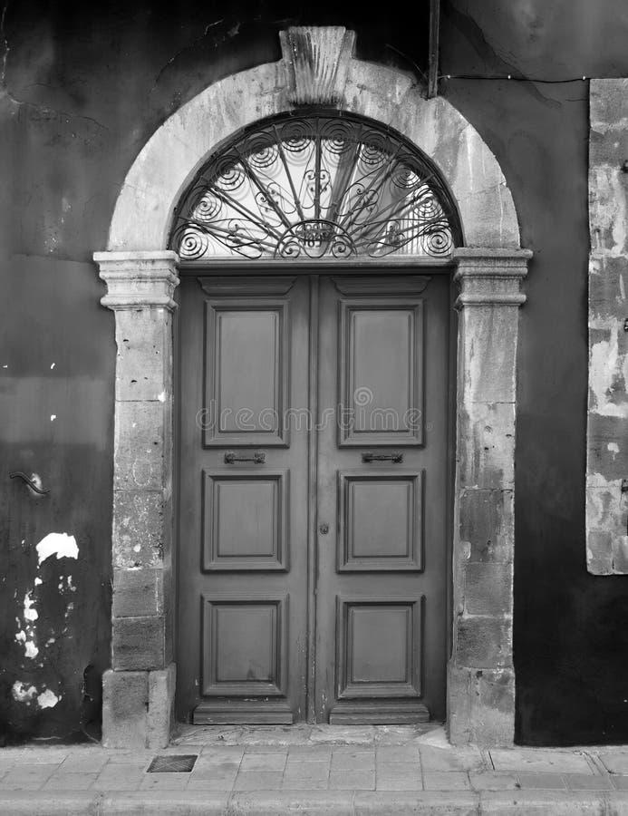 老后门的单色图象在一个被成拱形的石框架的与剥落的被绘的墙壁 库存照片