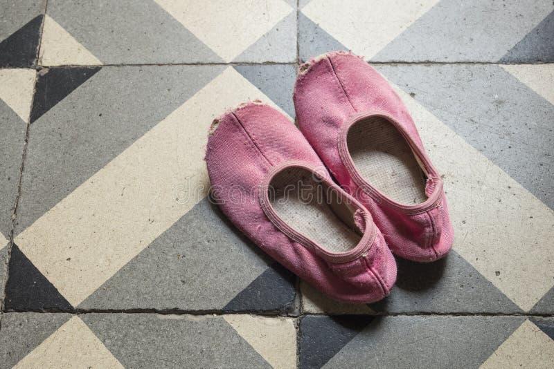 老和损坏的儿童` s桃红色跳舞拖鞋或鞋子细节  库存照片