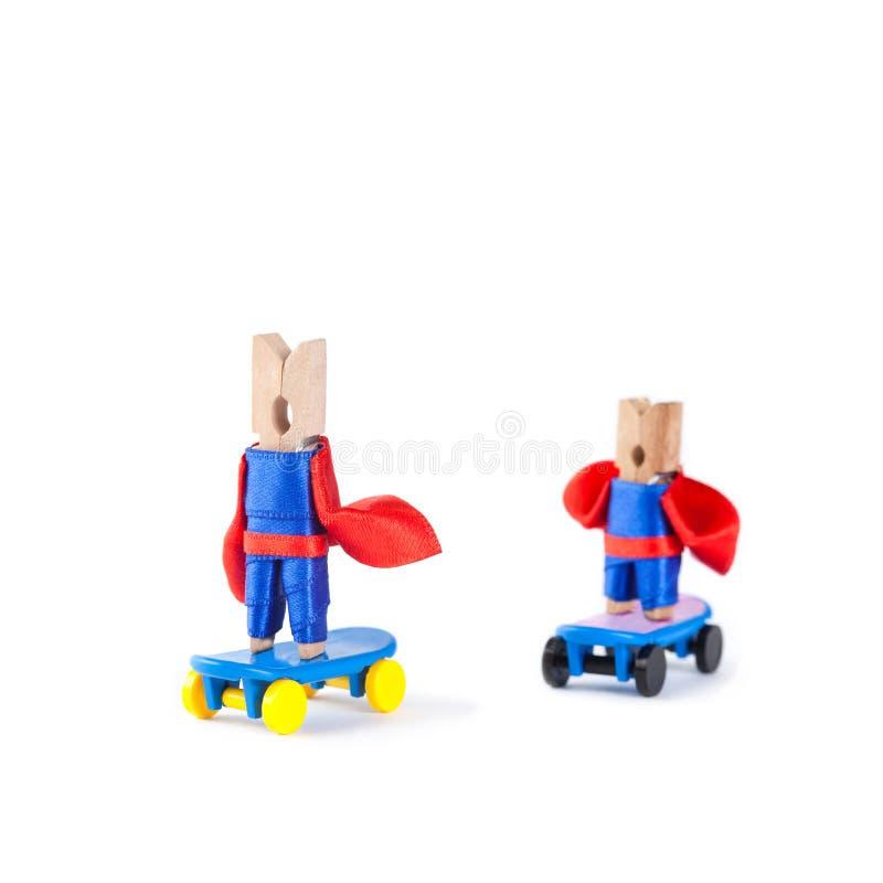 老和青年晒衣夹溜冰板者 团体性运动概念 滑冰的超级英雄 蓝色,红色衣服的英雄在蓝色冰鞋 库存照片