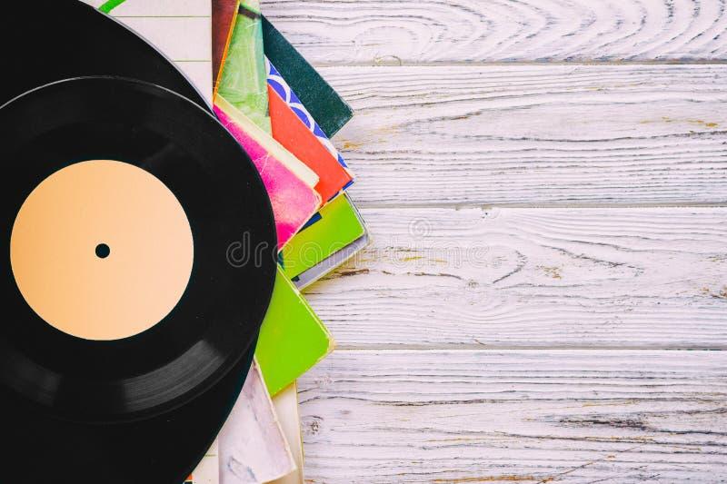 老唱片lp's的一汇集的减速火箭的被称呼的图象与袖子的在木背景有拷贝空间顶视图定了调子 免版税库存照片
