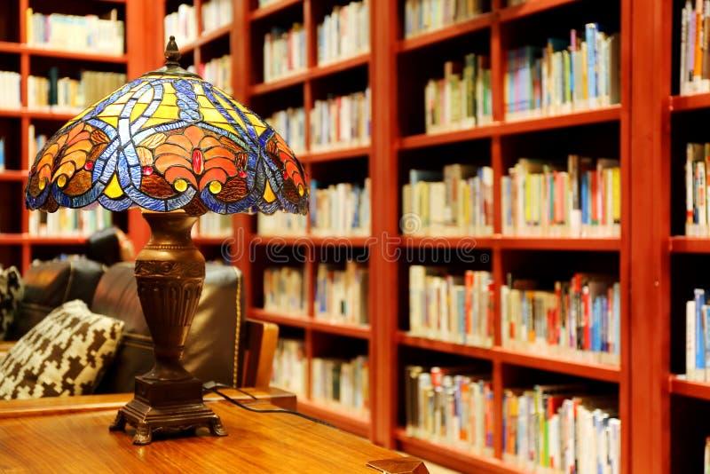 老图书馆阅览室、葡萄酒台灯、书和书架的概念在图书馆里 免版税库存照片
