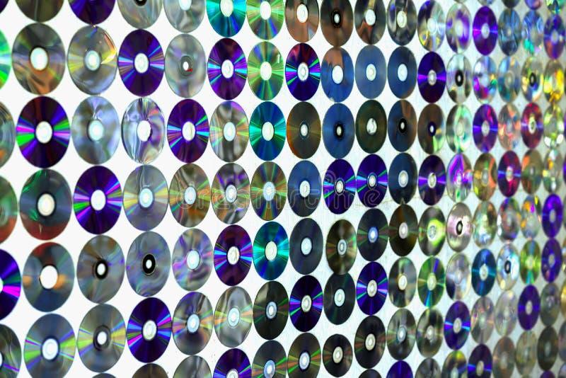老圆盘CD在有有多彩多姿的五颜六色的反射的墙壁,现代背景上 库存图片