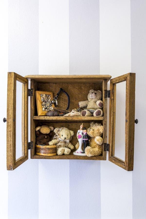 老土气木镶嵌墙上的摆饰橱、项目、玩具和记忆 垂直位置 免版税库存图片