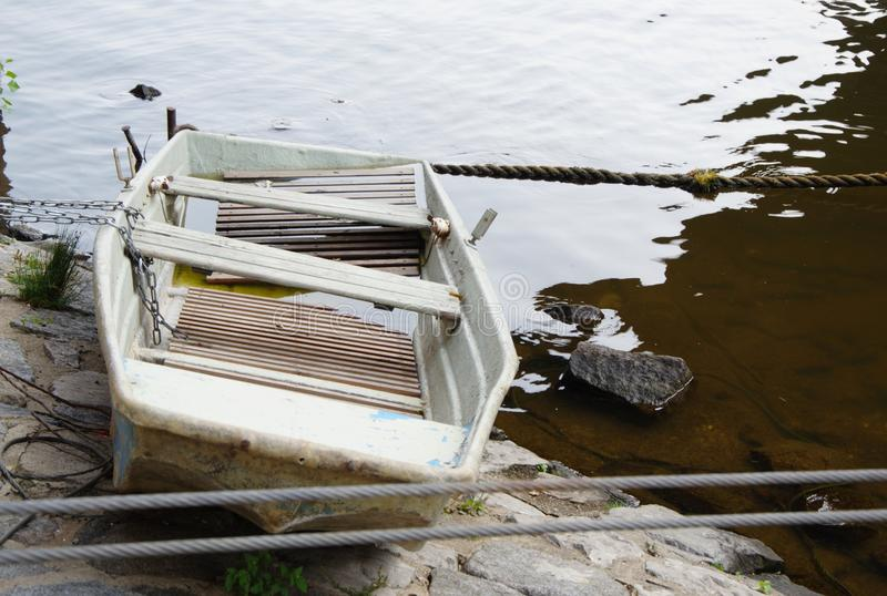 老土气白色小船用水里面在石河岸 库存图片