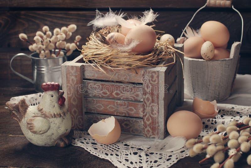 老土气静物画用在巢的鸡蛋在复活节的木箱 免版税库存照片