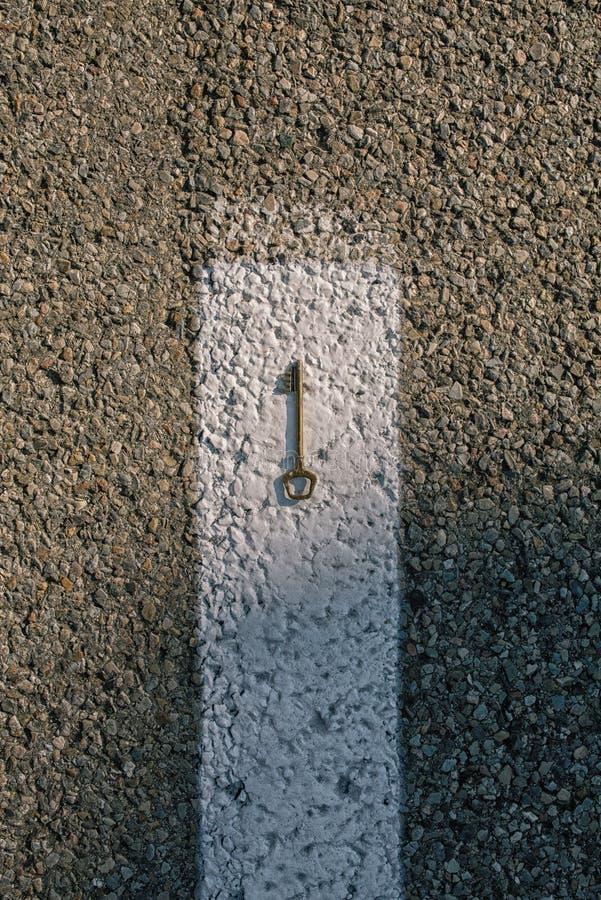 老在柏油路的葡萄酒黄铜门钥匙 免版税库存照片