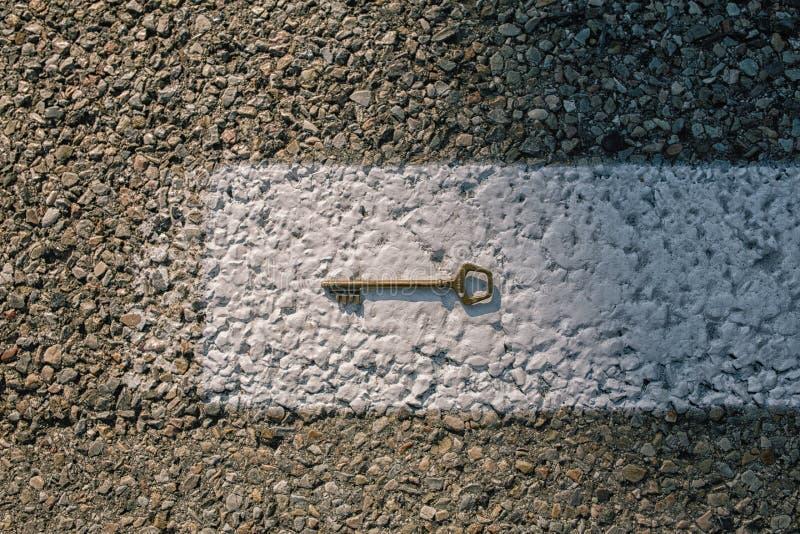 老在柏油路的葡萄酒黄铜门钥匙 图库摄影