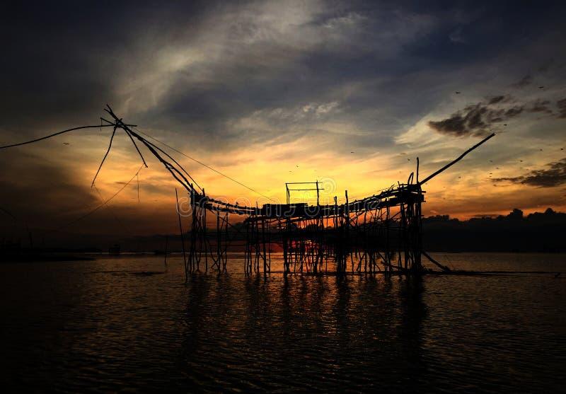 老在湖的文化传统钓鱼剪影由在早晨时间日出的木方形的抄网  免版税库存图片