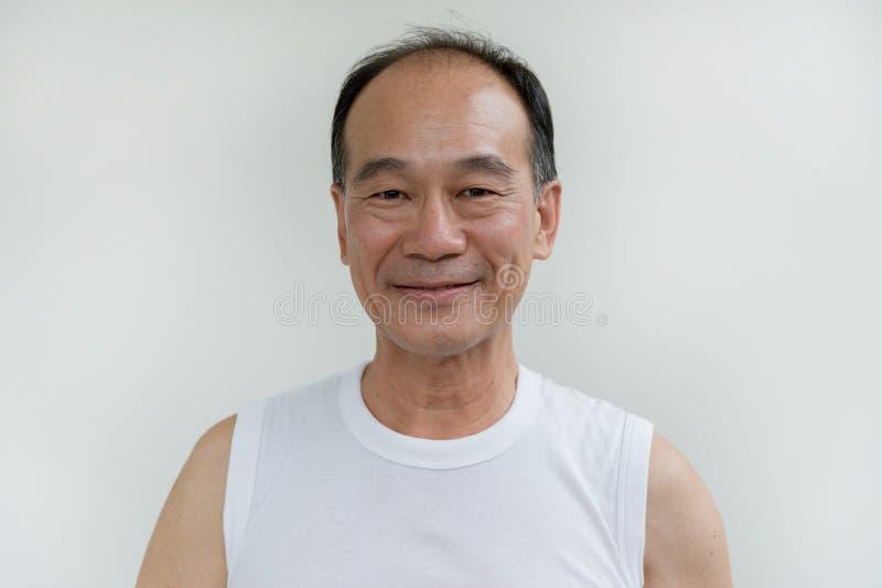 老在白色背景的人亚洲穿戴白色衬衣画象  图库摄影