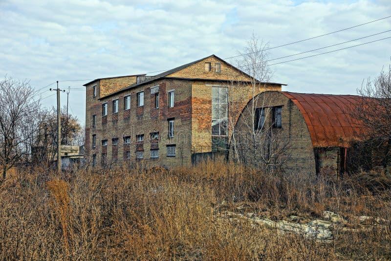 老在草丛林的砖工厂厂房  图库摄影