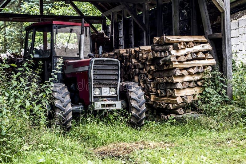 老在被堆积的德国乡下老被放弃的谷仓木柴木头的拖拉机正面图 免版税库存图片