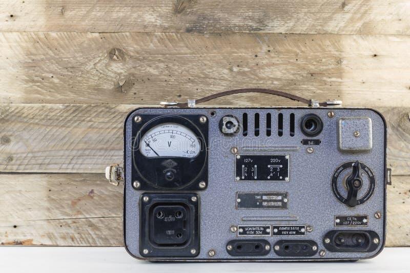 老在被风化的木背景的葡萄酒电安定器 减速火箭的电压调整器 库存照片
