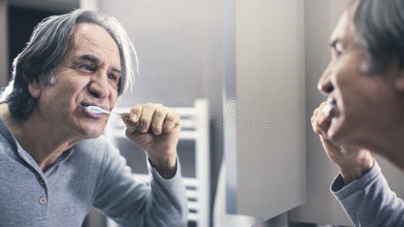 老在镜子前面的人掠过的牙 免版税库存照片
