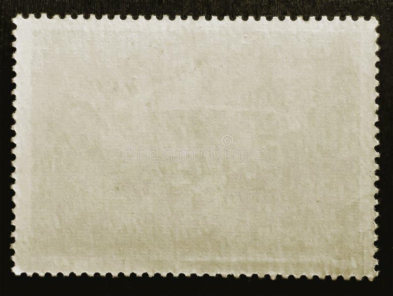 老在黑背景隔绝的难看的东西纹理纸张贴的邮票反面 关闭 复制空间 免版税图库摄影