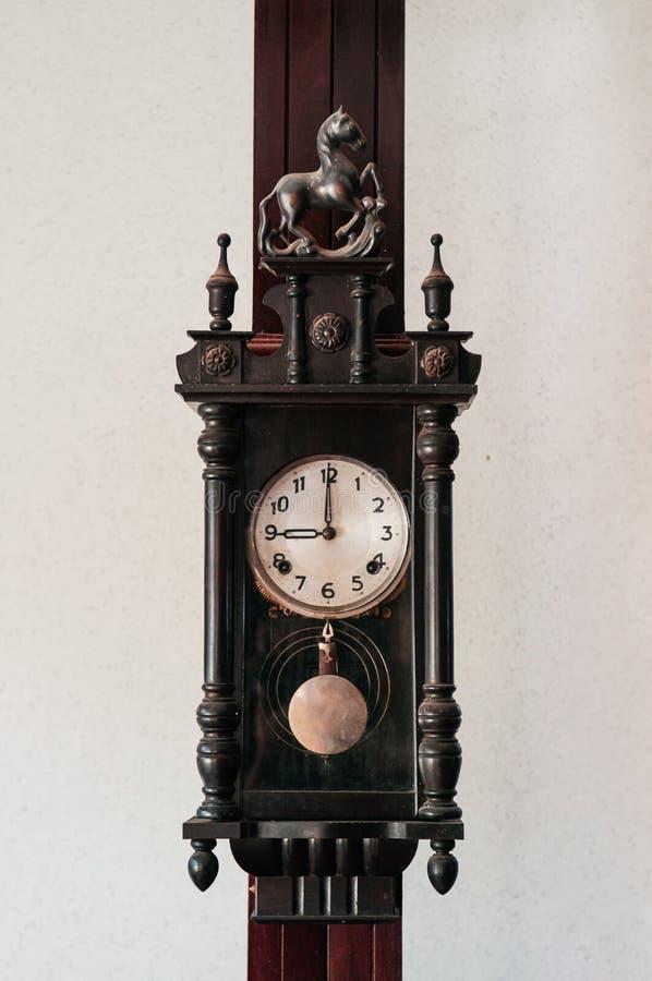 老垂悬在木柱子的葡萄酒祖父木壁钟 免版税库存图片