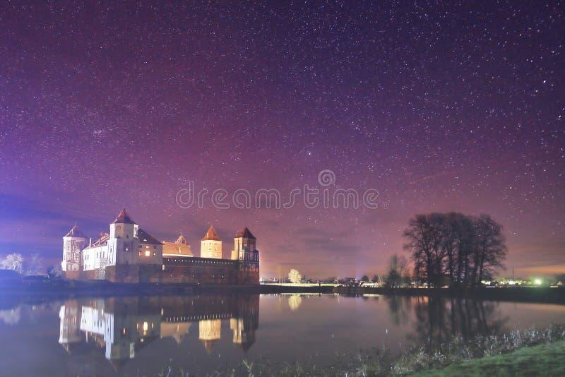 老城堡的夜风景在满天星斗的天空和湖的背景中 免版税库存图片