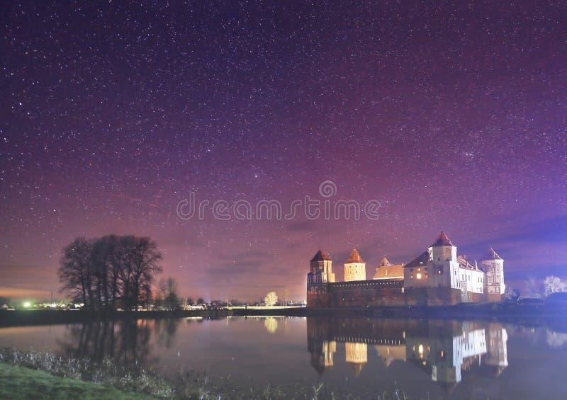 老城堡的夜风景在满天星斗的天空和湖的背景中 图库摄影