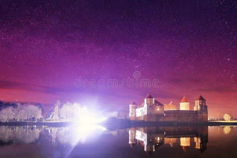 老城堡的夜风景在满天星斗的天空和湖的背景中 免版税图库摄影