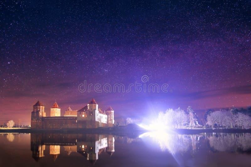 老城堡的夜风景在满天星斗的天空和湖的背景中 免版税库存照片