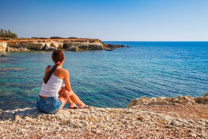 老城堡的美丽的旅游妇女在陆间海海岸帕福斯,塞浦路斯 明亮的日落光 免版税库存图片