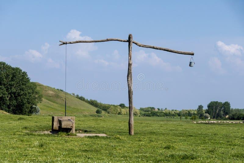 老塞尔维亚打扫井和桔槔在绿色草甸 图库摄影